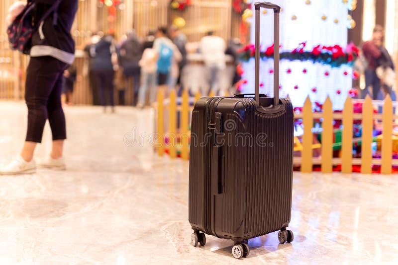 Saco da bagagem com o grupo de pessoas que verifica dentro na entrada do hotel no fundo do borrão foto de stock