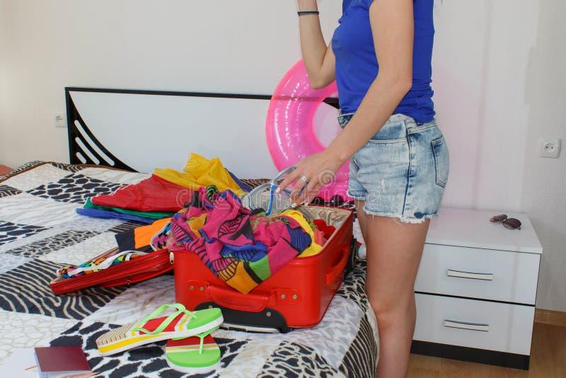 Saco da embalagem da menina para o curso Mulher com a mala de viagem que senta-se na cama no hotel foto de stock