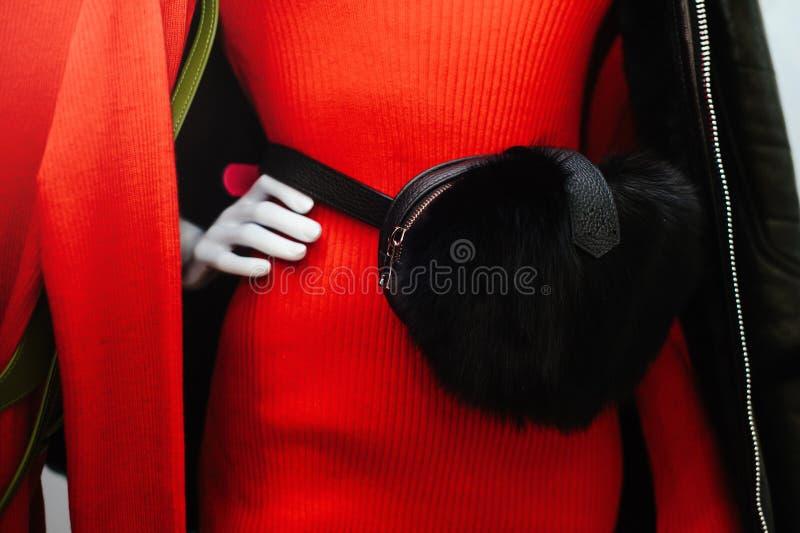 Saco da pele do couro do ` s das mulheres elegantes em uma mulher em um vestido vermelho venda dos bens de couro fotografia de stock