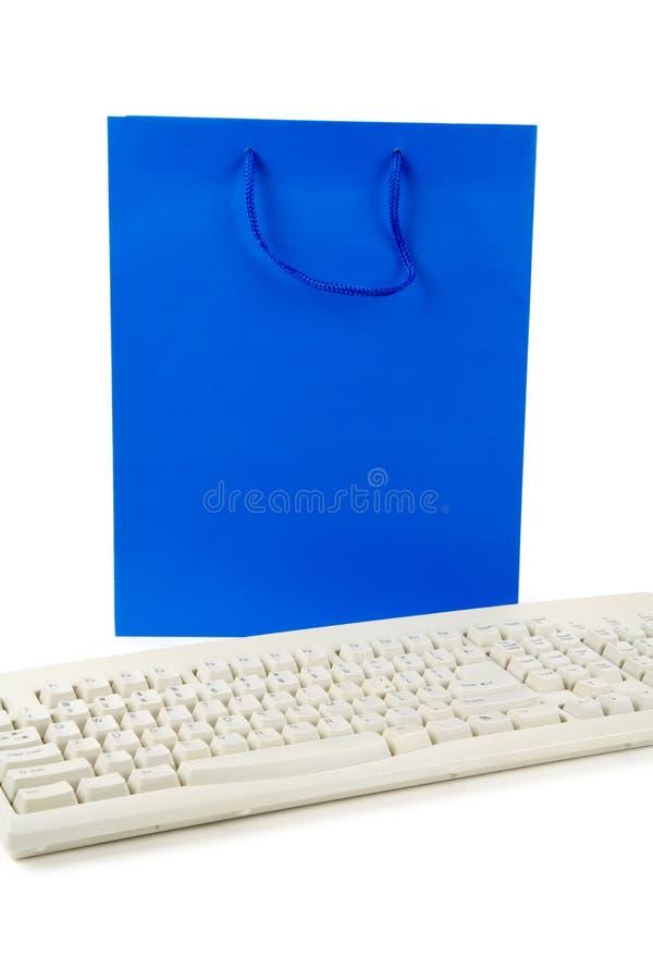 Saco de compra e teclado de computador azuis imagem de stock