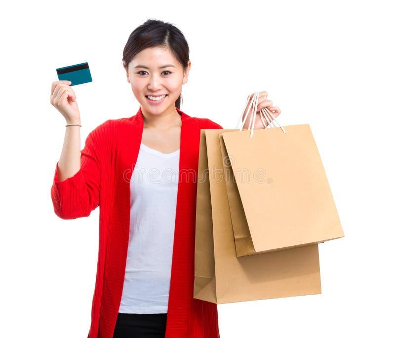 Saco de compras da posse da mulher e cartão de crédito asiáticos imagem de stock