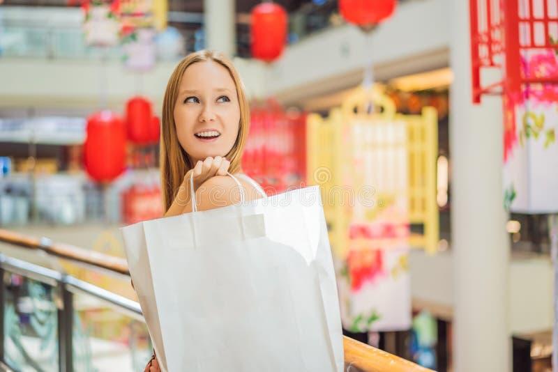 Saco de compras da posse da mulher na perspectiva das lanternas vermelhas chinesas pelo ano novo chinês Venda grande em honra de imagens de stock