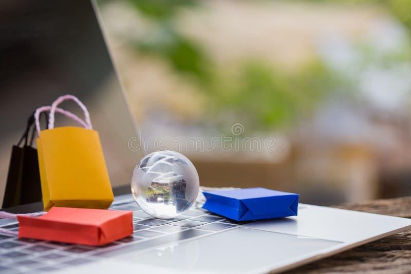 Saco de compras de papel colorido no trole no portátil imagens de stock royalty free