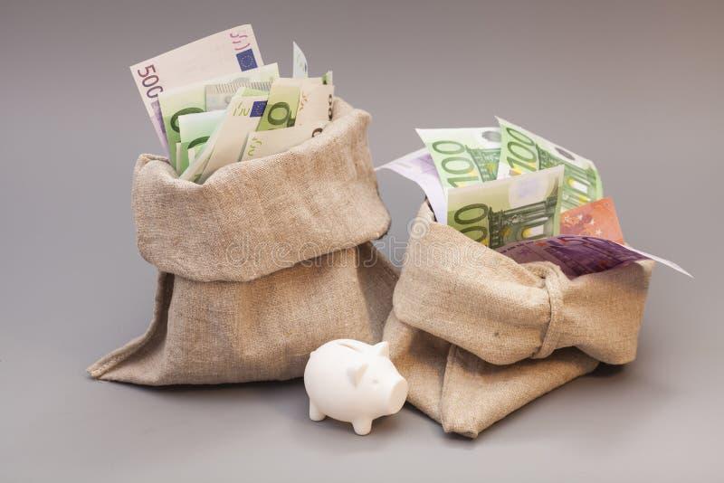 Saco de dois dinheiros com euro e mealheiro fotos de stock royalty free