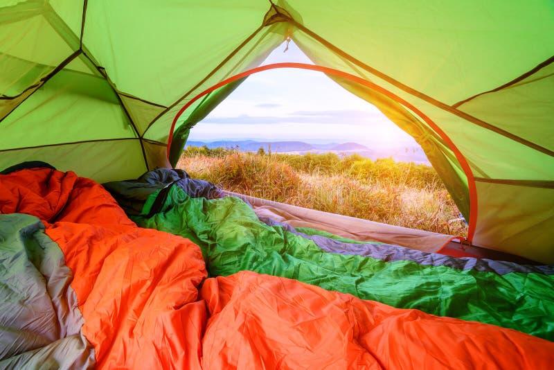 Saco de dormir dentro de una tienda que mira hacia fuera con la visión a través de la puerta de atrás foto de archivo libre de regalías
