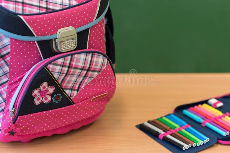 Saco de escola e caixa de lápis femininos cor-de-rosa em uma mesa contra o greenboard imagens de stock royalty free
