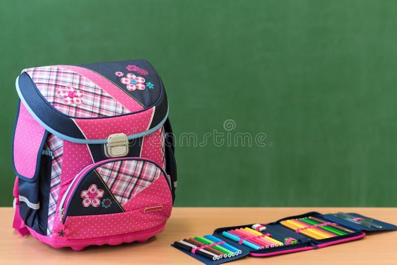 Saco de escola e caixa de lápis femininos cor-de-rosa em uma mesa contra o greenboard Primeiro dia da escola fotografia de stock