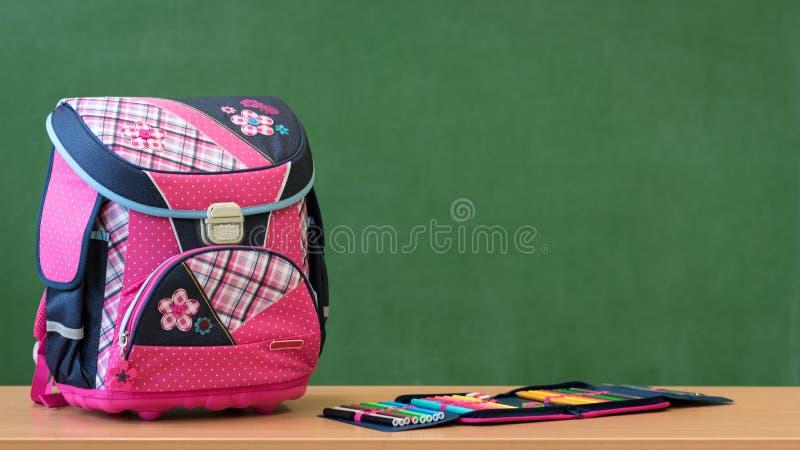 Saco de escola e caixa de lápis femininos cor-de-rosa em uma mesa contra a placa verde Primeiro dia da escola fotografia de stock