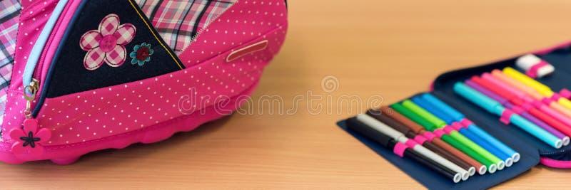 Saco de escola e caixa de lápis femininos cor-de-rosa em uma mesa Primeiro dia do conceito da escola fotografia de stock