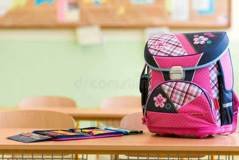 Saco de escola e caixa de lápis femininos cor-de-rosa em uma mesa em uma sala de aula vazia fotos de stock royalty free