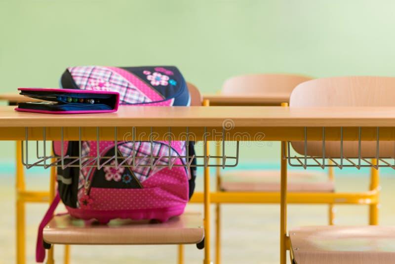 Saco de escola e caixa de lápis femininos cor-de-rosa em uma mesa em uma sala de aula vazia Primeiro dia da escola fotografia de stock