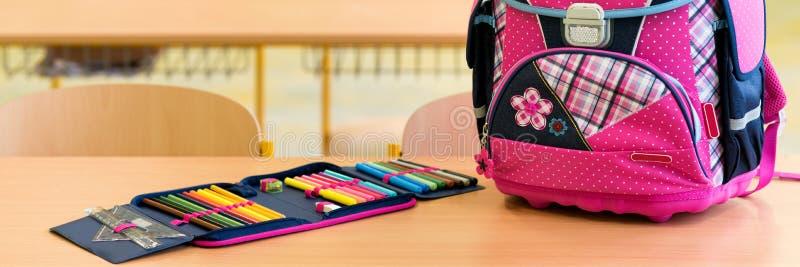 Saco de escola e caixa de lápis femininos cor-de-rosa em uma mesa em uma sala de aula vazia Primeiro dia do conceito da escola foto de stock royalty free