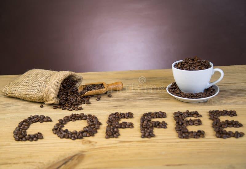 Saco de feijões de café na tabela de madeira imagem de stock