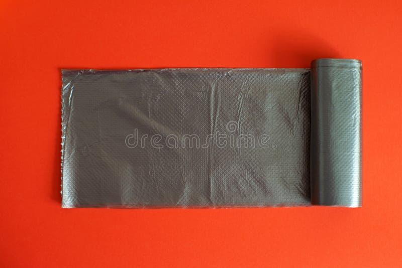 Saco de lixo preto em um fundo vermelho foto de stock royalty free