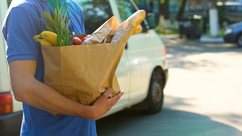 Saco de mantimento com os bens saborosos frescos, serviço da terra arrendada do trabalhador da entrega do supermercado imagens de stock