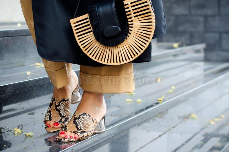 Saco de moda fechado em mãos femininas Garota caminha pela cidade ao ar livre Imagem moderna e feminina, estilo Mulher em um sonh fotografia de stock royalty free