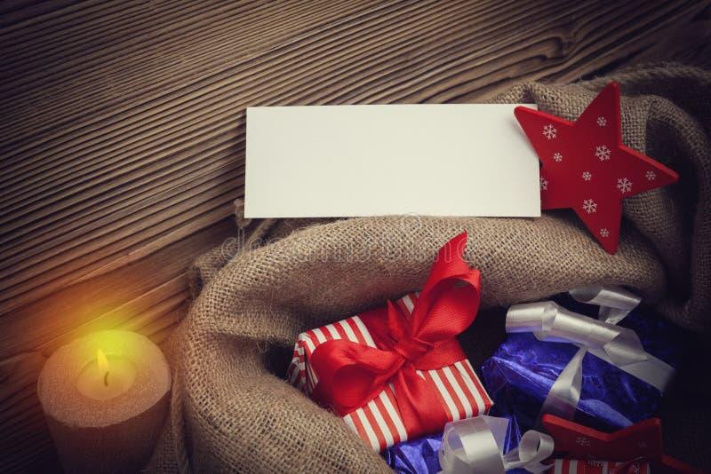 Saco de Navidad con los regalos y la tarjeta de felicitación en blanco imagen de archivo libre de regalías