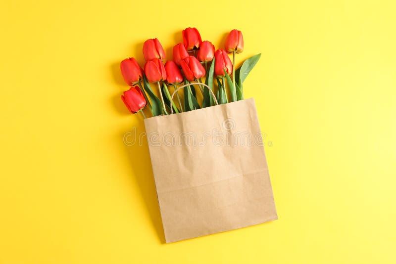 Saco de papel com as tulipas vermelhas bonitas no fundo amarelo imagens de stock