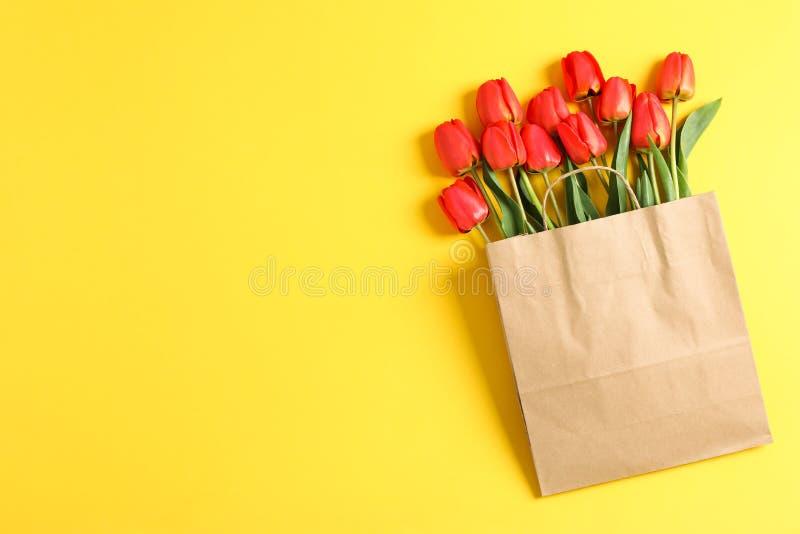 Saco de papel com as tulipas vermelhas bonitas no fundo amarelo imagem de stock royalty free