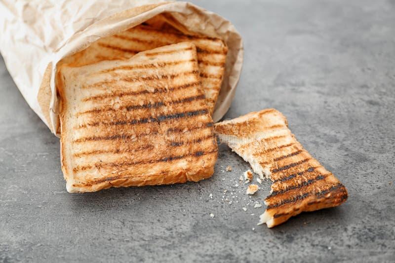 Saco de papel com pão brindado no fundo cinzento imagens de stock