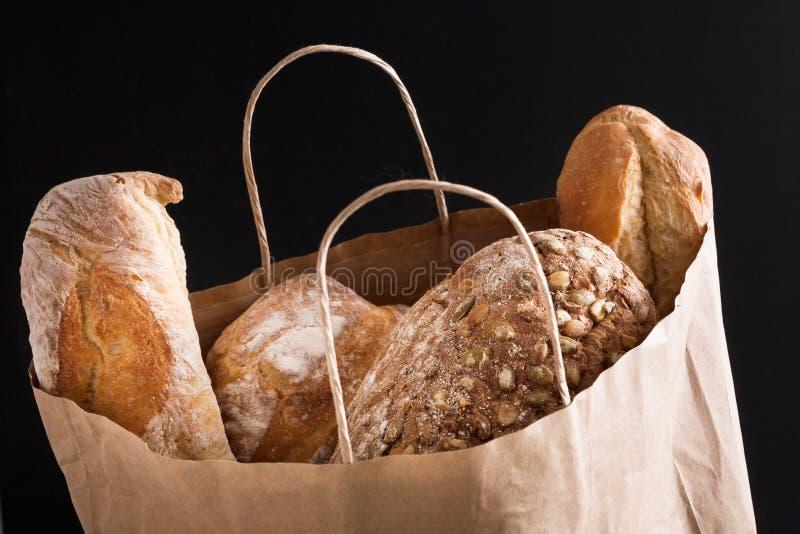 Saco de papel com a variedade do pão no fundo preto fotografia de stock royalty free