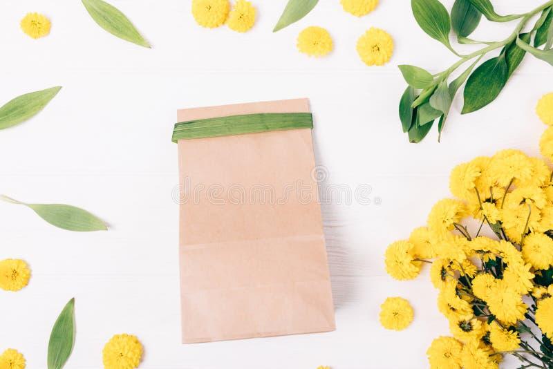 Saco de papel do presente entre a composição colocada lisa do ramalhete amarelo fotos de stock royalty free