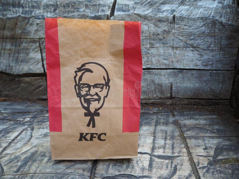 Saco de papel de Kentucky Fried Chicken em um banco de madeira cinzento KFC ? uma corrente de restaurante do fast food sediada no imagens de stock