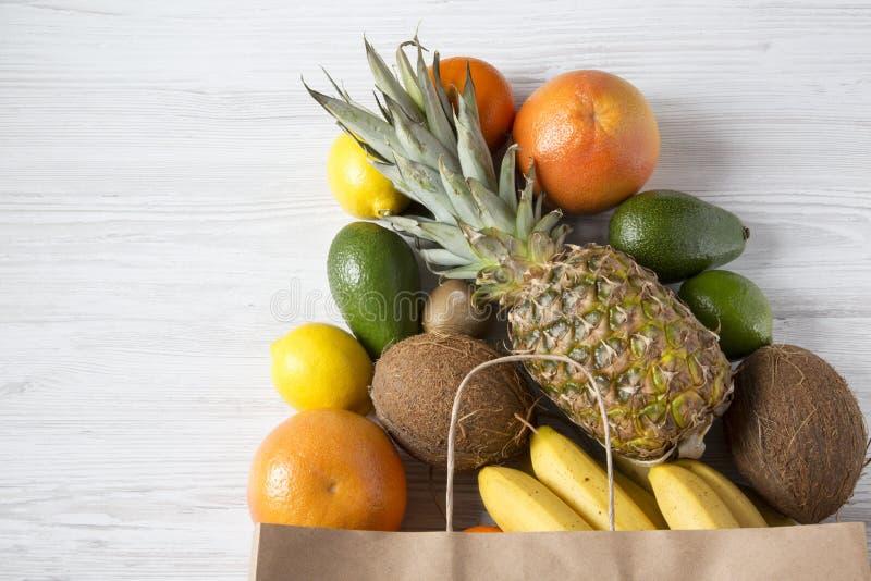 Saco de papel de vários frutos exóticos no fundo de madeira branco, vista superior Copie o espaço imagem de stock