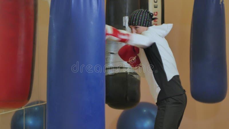 Saco de perfuração do treinamento da mulher do encaixotamento na série apta do kickboxer do corpo da força feroz do estúdio da ap fotografia de stock royalty free