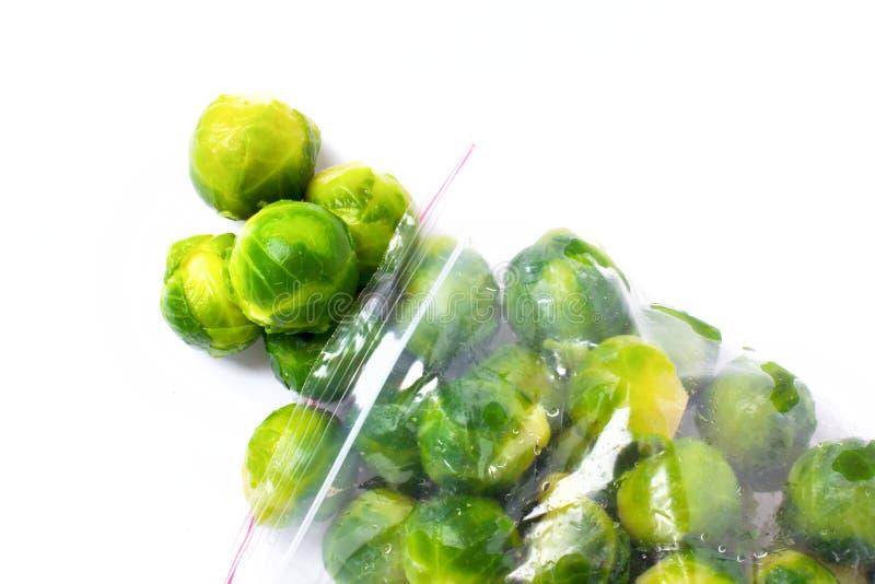 Saco de plástico com as couves-de-Bruxelas congeladas isoladas no branco veget fotografia de stock royalty free