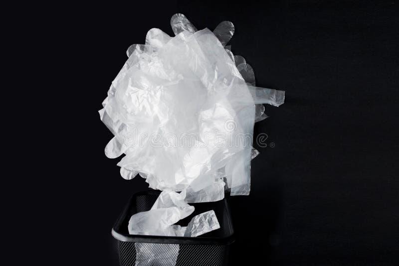 Saco de plástico com punhos, luvas no escaninho em um fundo preto Saco de plástico usado para reciclar Conceito - ecologia, plane imagens de stock royalty free