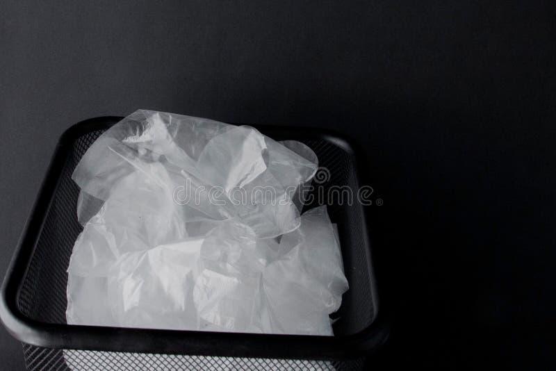 Saco de plástico com punhos, luvas no escaninho em um fundo preto Saco de plástico usado para reciclar Conceito - ecologia, plane imagens de stock