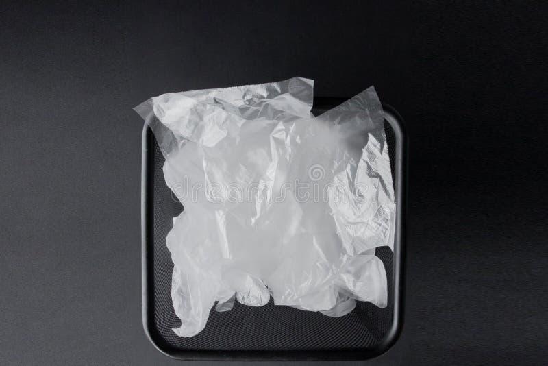 Saco de plástico com punhos, luvas no escaninho em um fundo preto Saco de plástico usado para reciclar Conceito - ecologia, plane fotografia de stock