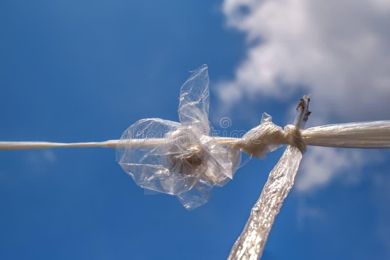 Saco de plástico torcido no céu azul fotografia de stock