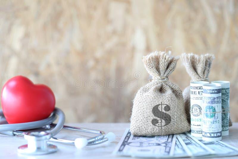 Saco do dinheiro com cédula e estetoscópio com coração vermelho em de madeira imagens de stock