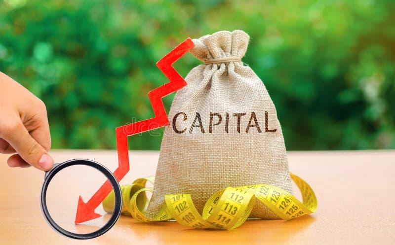 Saco do dinheiro com o capital e a seta da palavra para baixo Queda no nível de capital autorizado Deixe cair em retorno na equid fotografia de stock royalty free