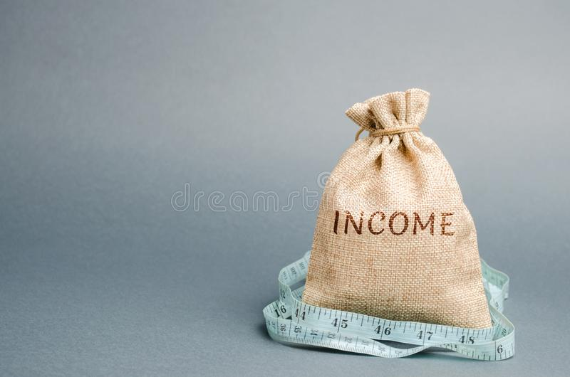 Saco do dinheiro com a renda da palavra e a fita de medição Rendimento reduzido e lucros Or?amento reduzido Perda de dinheiro uns imagens de stock