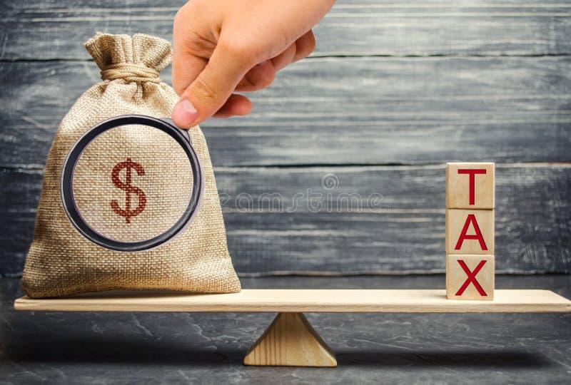 Saco do dinheiro e blocos de madeira com o imposto da palavra nas escalas O conceito de pagar impostos e reembolso de d?bito Regi imagens de stock royalty free
