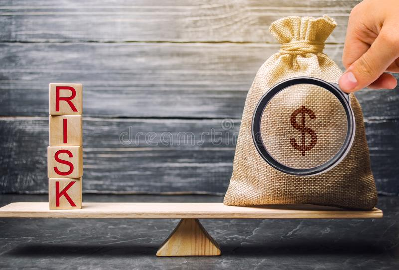 Saco do dinheiro e blocos de madeira com o risco da palavra O conceito do risco financeiro Riscos justificados Investimento em um imagem de stock