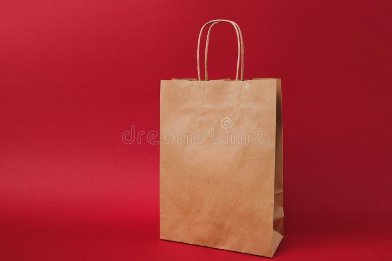 Saco do pacote, saco de papel vazio vazio claro marrom do ofício para afastado isolado no fundo vermelho brilhante Produtos alime imagem de stock royalty free