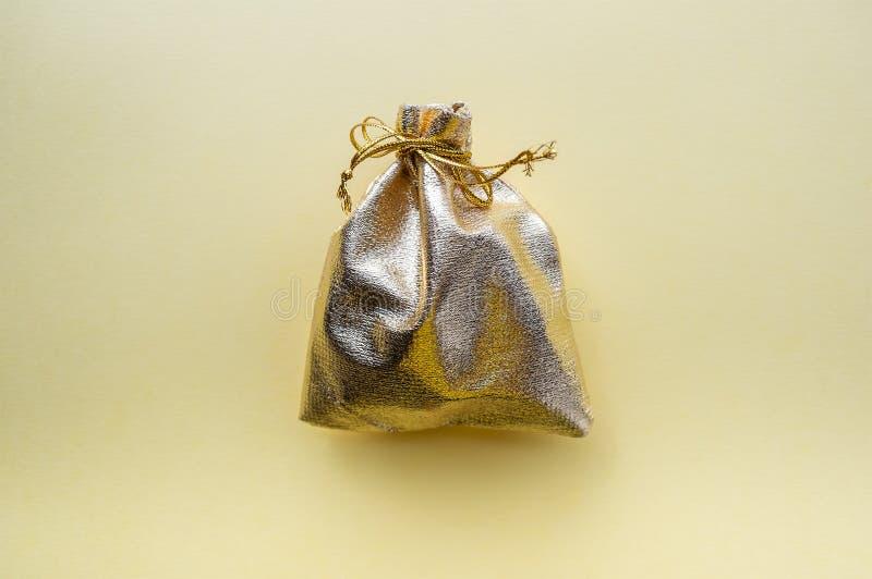 Saco do presente da tela dourada em um fundo amarelo O conceito do feriado fotos de stock