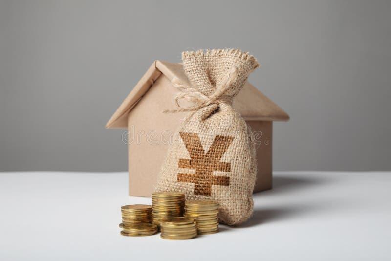 Saco do vintage com sinal do yuan e moedas amarelas no fundo da figura do ofício da casa Seguro e hipotecas da casa compra fotografia de stock