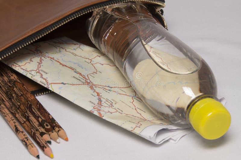 Saco do zíper com a garrafa da água, do mapa e dos lápis fotos de stock