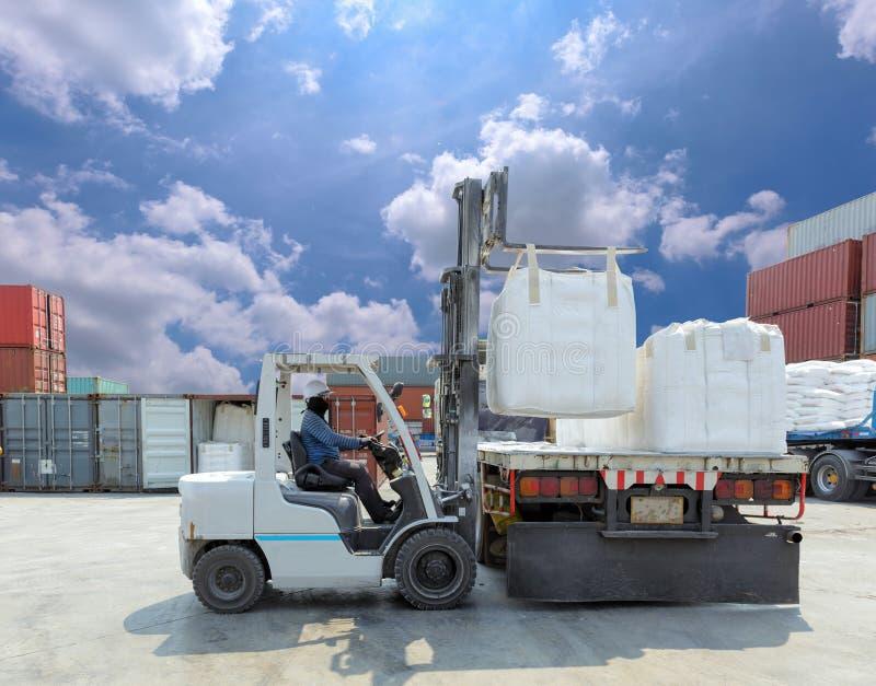 Saco grande movente do motorista da empilhadeira ao caminhão na jarda imagens de stock royalty free