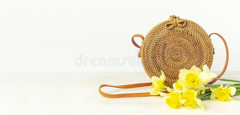 Saco redondo org?nico natural feito a m?o elegante do rattan, narciso amarelo ou flores do narciso amarelo na configura??o lisa d fotos de stock royalty free