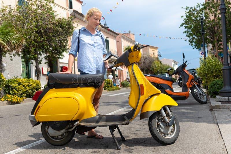Saco vestindo da trouxa do turista fêmea novo que estaciona o 'trotinette' retro urbano do vintage amarelo italiano tradicional n foto de stock