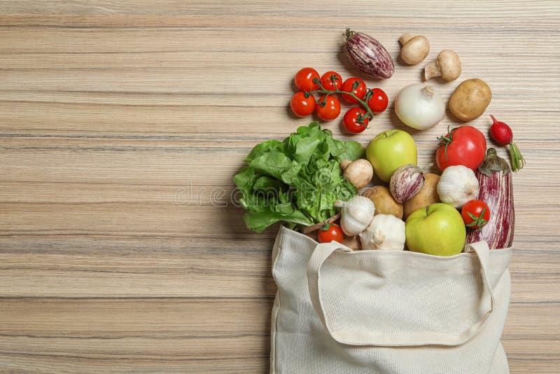 Saco virado de pano com vegetais e maçãs no fundo de madeira, configuração lisa imagens de stock