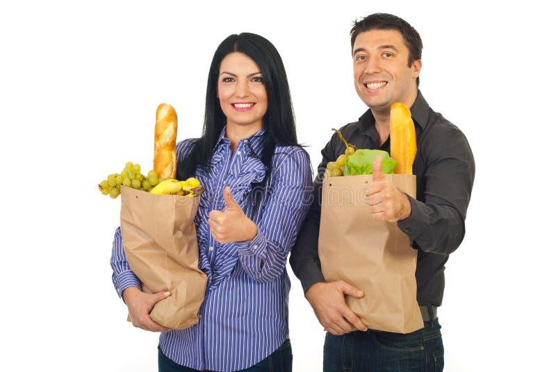 Sacos bem sucedidos da terra arrendada da família com alimento imagem de stock royalty free