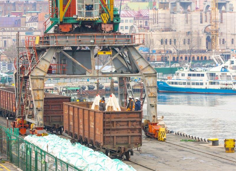 Sacos carregados trabalhadores no porto imagem de stock royalty free
