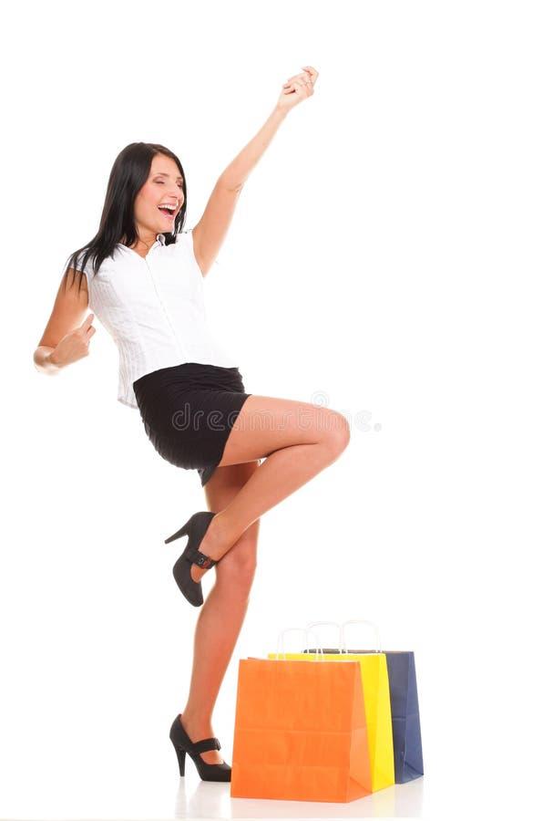 Sacos de compra carreg da mulher nova de encontro ao branco foto de stock royalty free